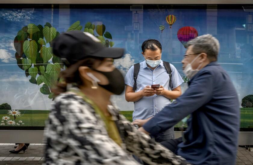 یک مسافر چینی هنگام انتظار در ایستگاه اتوبوس ، تلفن همراه خود را بررسی می کند