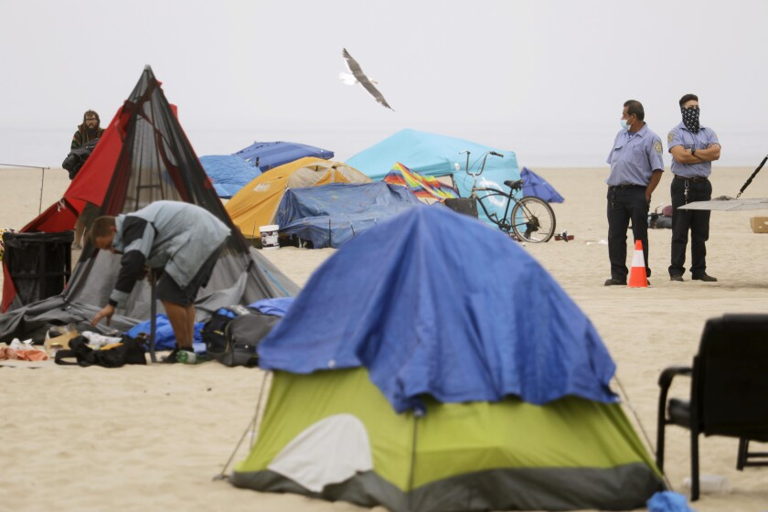 Homeless people break down their encampments on Venice Beach while two county employees watch.
