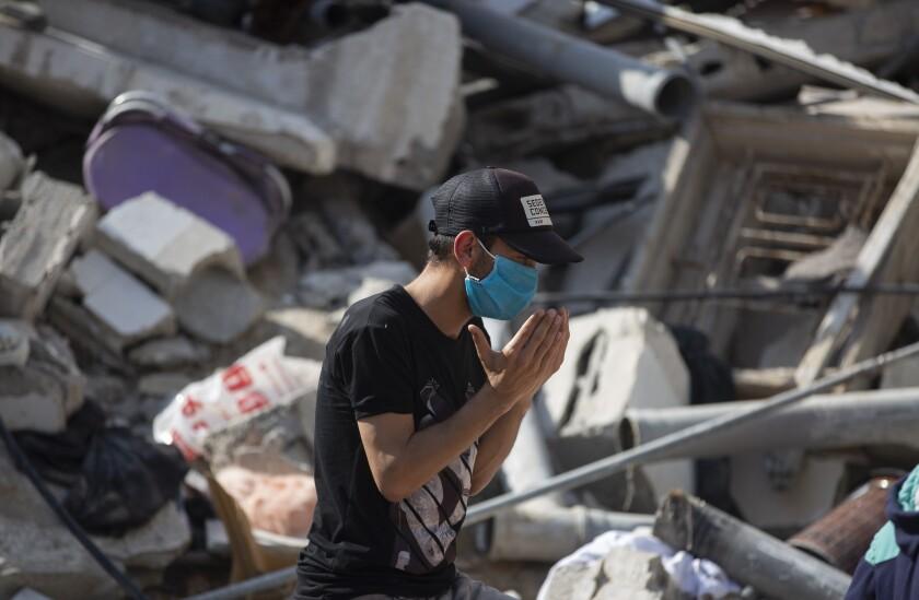 Un palestino reza frente a los escombros de un edificio
