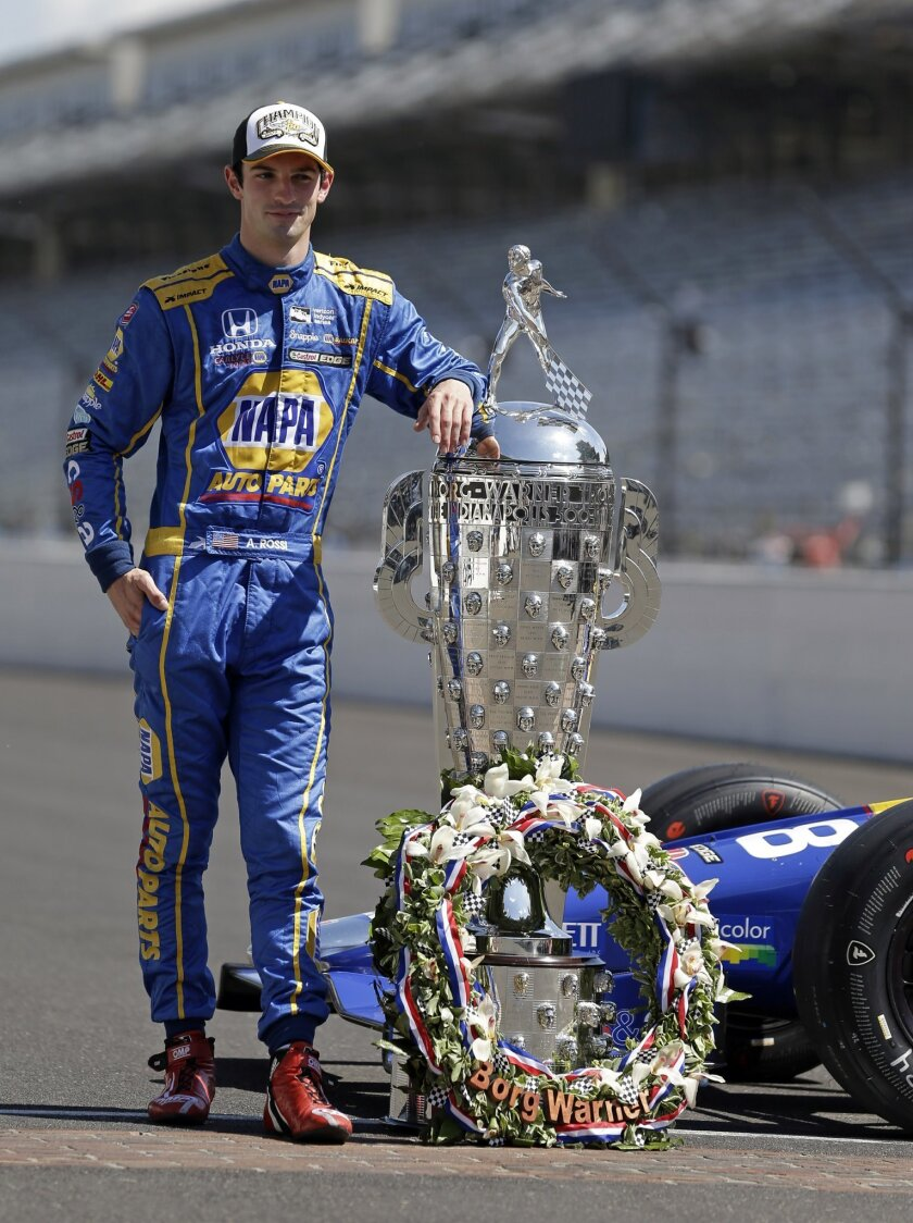 Indianapolis 500 champion Alexander Rossi poses with the Borg-Warner Trophy during the traditional winners photo on the start/finish line at Indianapolis Motor Speedway in Indianapolis, Monday, May 30, 2016. Rossi won the 100th running of the Indianapolis 500 auto race on Sunday. (AP Photo/Michael