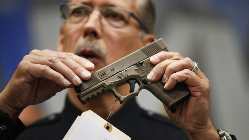 Los Angeles Police Det. Ben Meda holds a handgun during a news conference at the Hollywood station Thursday. More than 40 firearms were seized in a recent joint task force operation, authorities said.