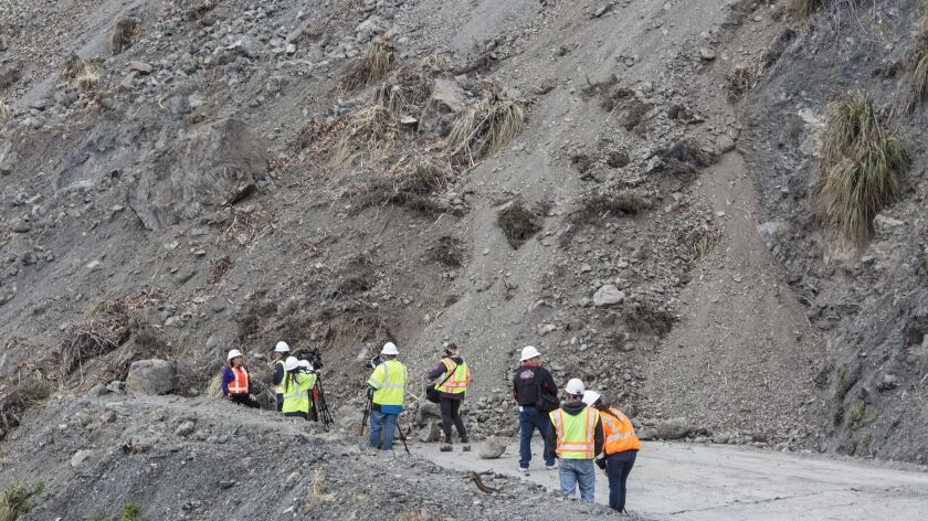 Caltrans officials and media members gather on Highway 1 where a landslide cut off the road north of Ragged Point.