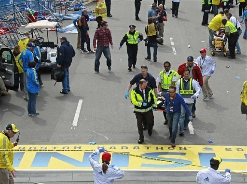 Medical workers wheel the injured across the finish line during the 2013 Boston Marathon following an explosion in Boston, Monday, April 15, 2013. Two explosions shattered the euphoria of the Boston Marathon finish line on Monday, sending authorities out on the course to carry off the injured while