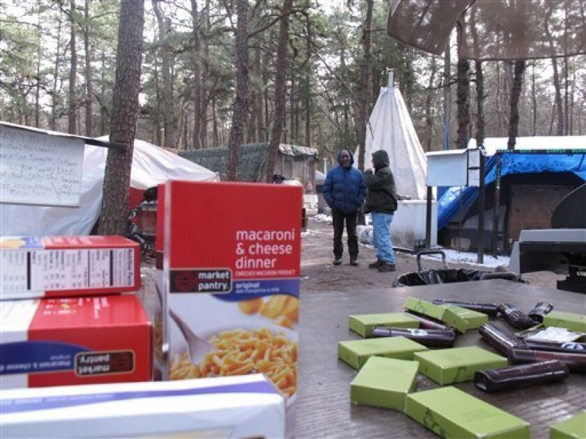 FILE - In this file photo of Feb. 4, 2013, boxes of macaroni and cheese and donated cosmetics sit on a table at Tent City, the encampment of homeless people in the woods of Lakewood, N.J., as camp residents talk in the background. Superior Court Judge Joseph Foster will hold a hearing Friday, March