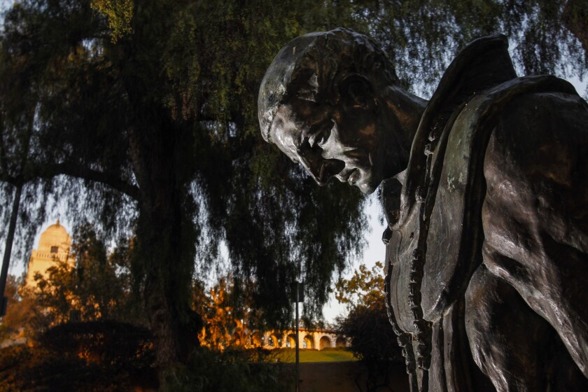 """A statue titled """"The Padre"""" is shown with the Junipero Serra Museum in the background at Presidio Park in San Diego."""