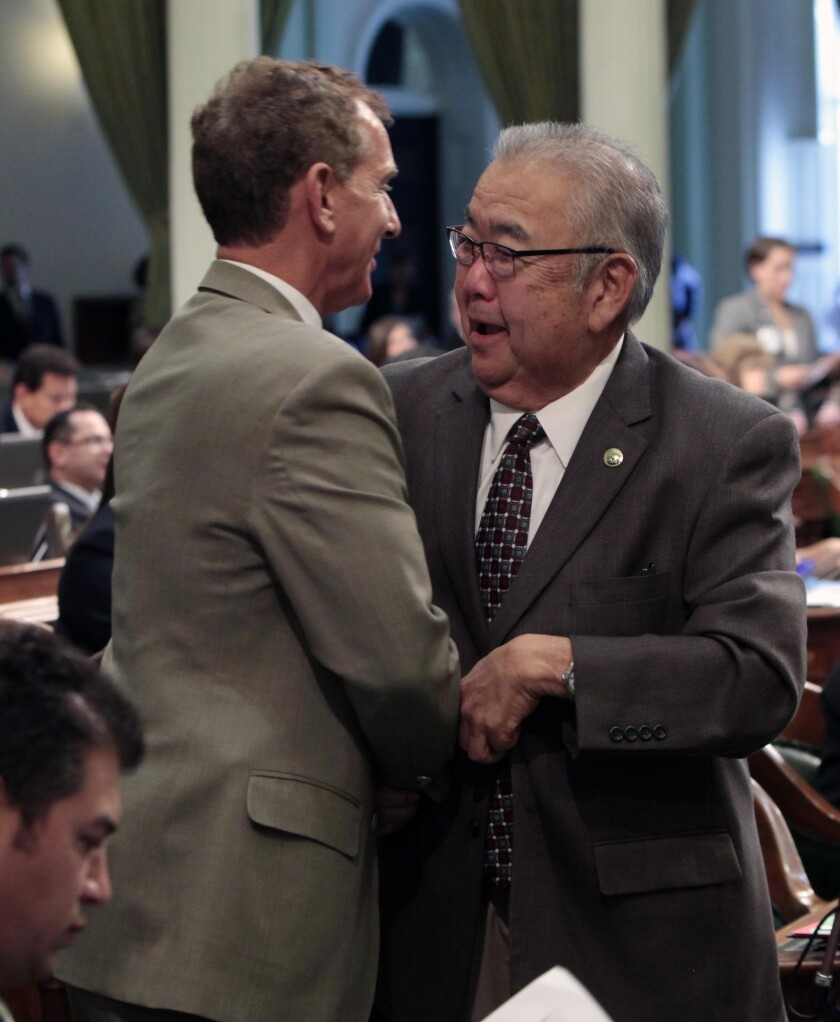 Then-Assemblyman Warren Furutani in 2012, being congratulated by then-Assemblyman Bob Wieckowski after his pension reform bill was approved by the Assembly.