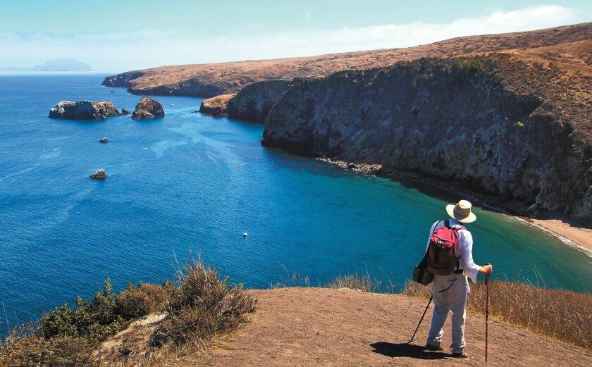 A hiker on Santa Cruz Island in the Channel Islands looks east toward Anacapa Island.