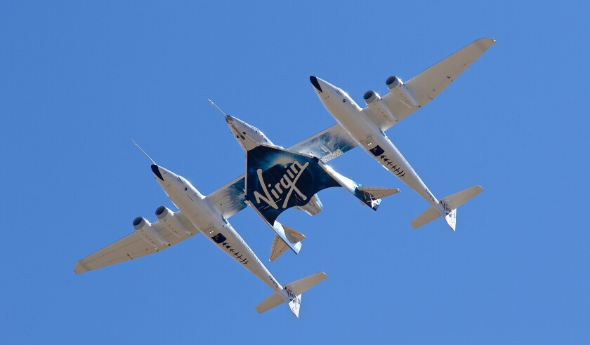 """FILE - In this Feb. 13, 2020, file photo, Virgin Galactic's VSS Unity departs Mojave Air & Space Port in Mojave, Calif. for the final time as Virgin Galactic shifts its SpaceFlight operations to New Mexico. Virgin Galactic said Thursday, Nov. 5, 2020, it expects to launch its first test spaceflight from New Mexico between Nov. 19-23. """"This will be the first-ever human spaceflight conducted from New Mexico,"""" Chief Executive Officer Michael Colglazier said in a statement. (Matt Hartman via AP, File)"""