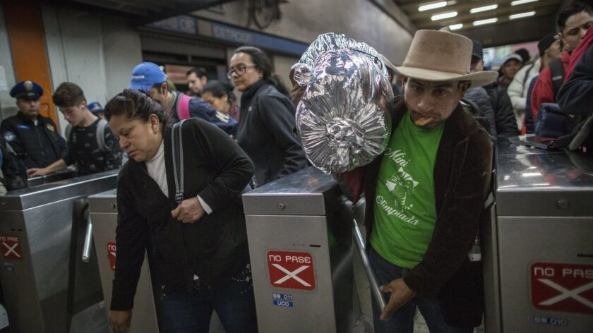 A Central American migrant passes through a subway turnstile after leaving the temporary shelter in
