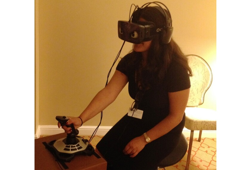 """Los Angeles Times reporter Saba Hamedy tests out the Dragon 2 Virtual Reality Flying Experience at a media event for """"How to Train Your Dragon 2,"""" at the Four Seasons Hotel in Beverly Hills."""