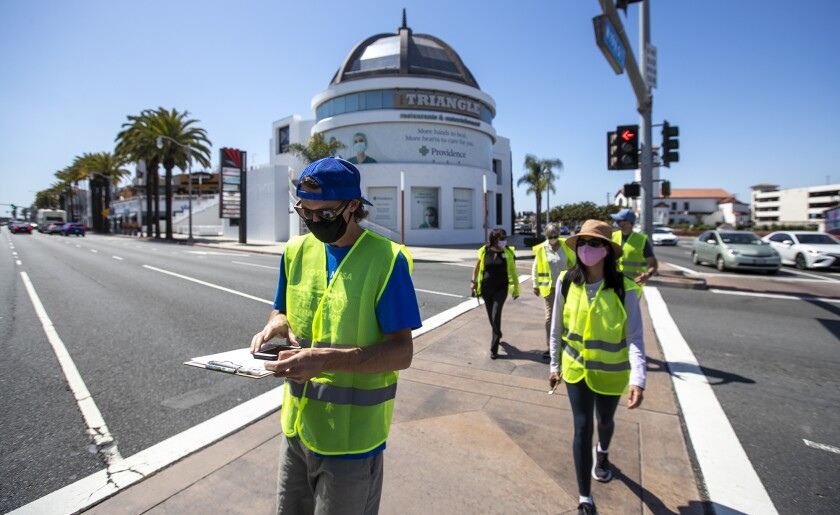 Consultants, city staff and officials cross Newport Boulevard in Costa Mesa during a walking audit.