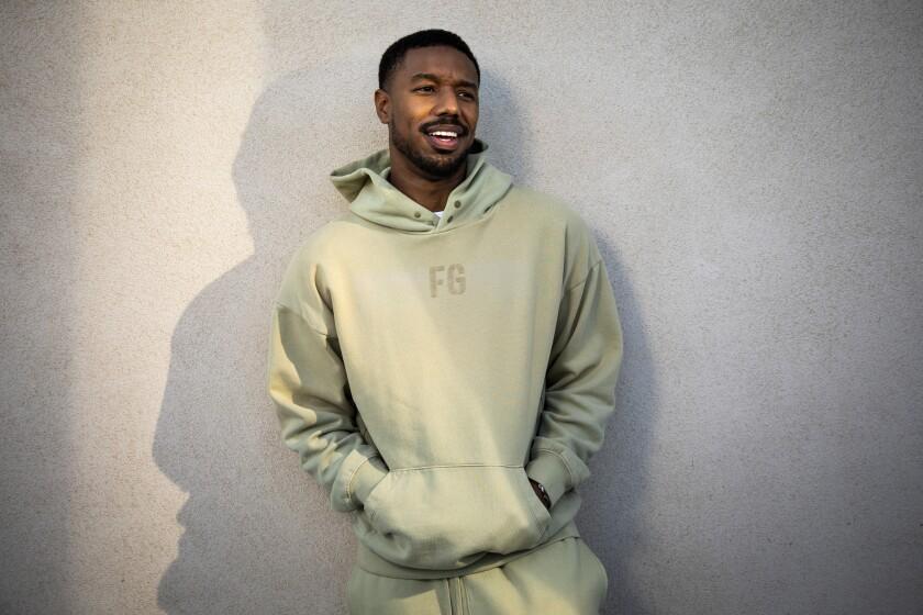 Michael B. Jordan smiles in a hoodie