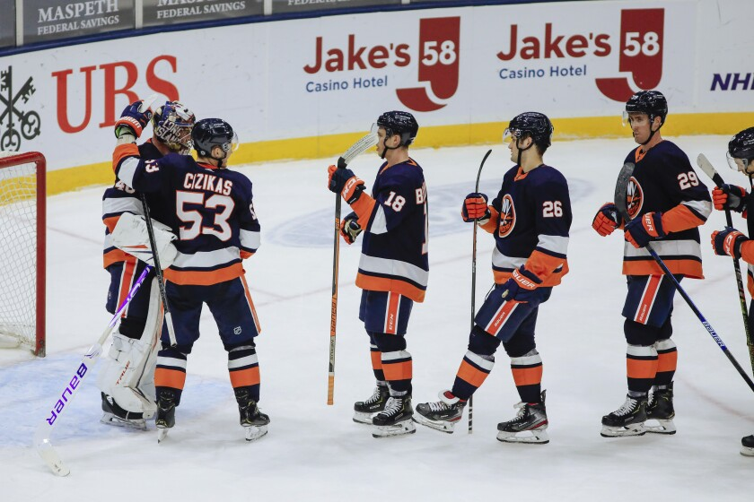 New York Islanders goalie Semyon Varlamov, left, is congratulated by teammates after their 5-2 win over the Buffalo Sabres in an NHL hockey game, Saturday, March 6, 2021, in Uniondale, NY. (AP Photo/Kevin Hagen).
