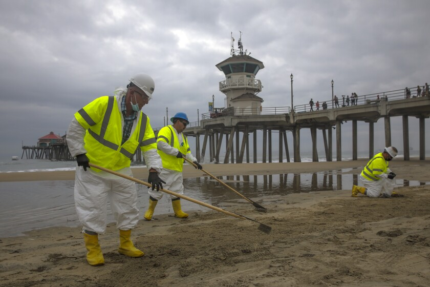 Workers in protective gear comb the Huntington Beach shoreline with the pier and a cloudy sky in the background