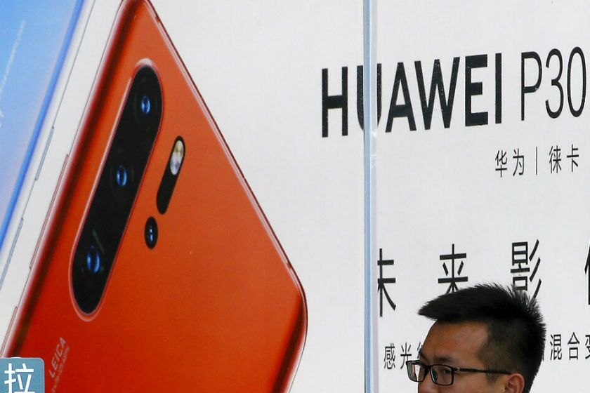 A staffer looks out from a Huawei retail store in Beijing.