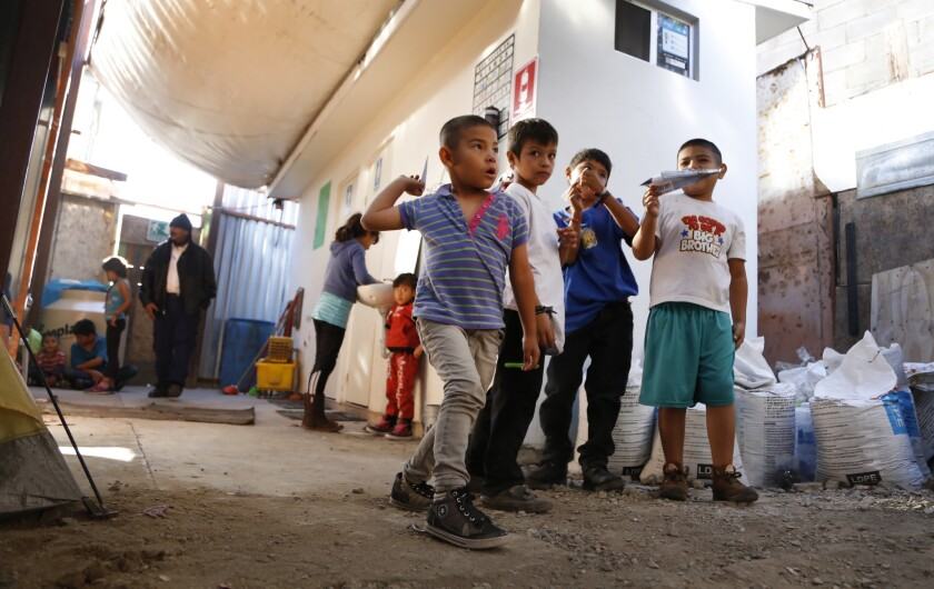 Boys play with paper airplanes inside a shelter in Tijuana.