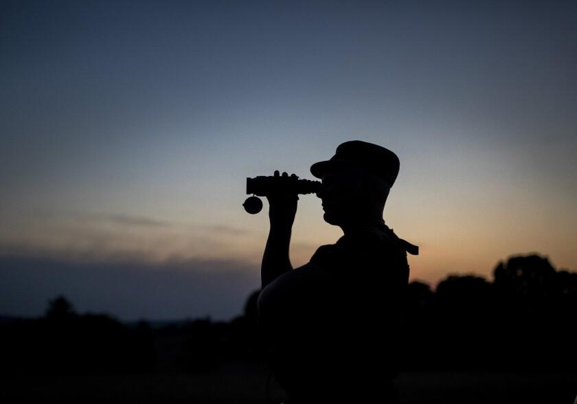 Border guard looking through binoculars