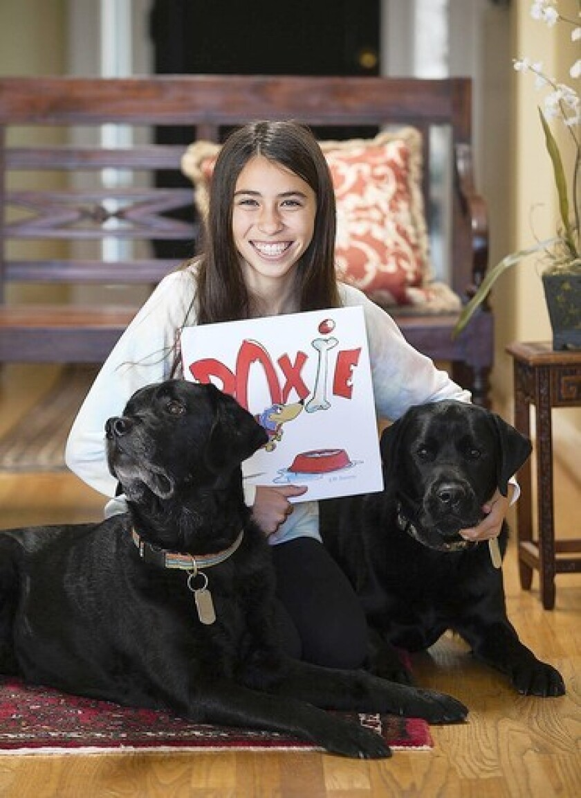 "Sammy Pickell, 14, recently had her story ""Doxie"" published as a picture book. She wrote the story in fifth grade. The family's two dogs Ned and Cooper, were a part of her inspiration for the book."