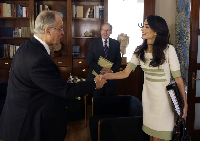 Lawyer Amal Alamuddin Clooney, right, shakes hands with Greek Culture Minister Constantinos Tassoulas during their meeting in Athens on Tuesday.