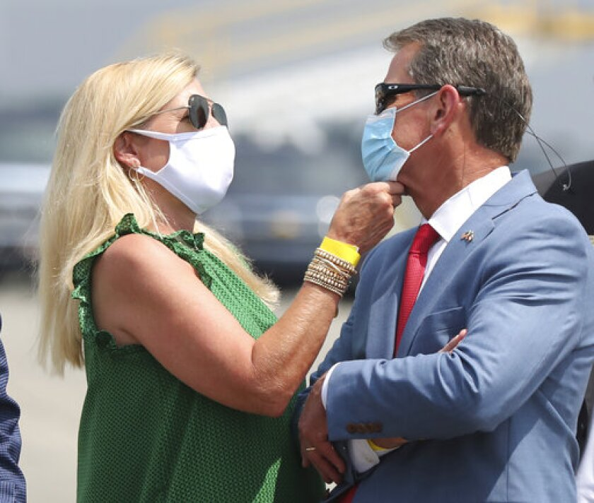 Georgia Gov. Brian Kemp has his mask adjusted by first lady Marty while waiting for President Donald Trump to arrive for his Georgia visit to talk about an infrastructure overhaul at the UPS Hapeville hub at Hartsfield-Jackson International Airport on Wednesday July 15, 2020 in Atlanta. (Curtis Compton/Atlanta Journal-Constitution via AP)