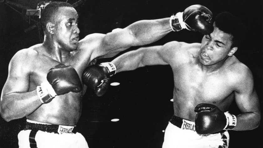 Heavyweight champion Sonny Liston, left, and Muhammad Ali exchange punches during their first fight in Miami on Feb. 25, 1964. Ali, then known as Cassius Clay, defeated Liston by technical knockout in the seventh round to claim the title.