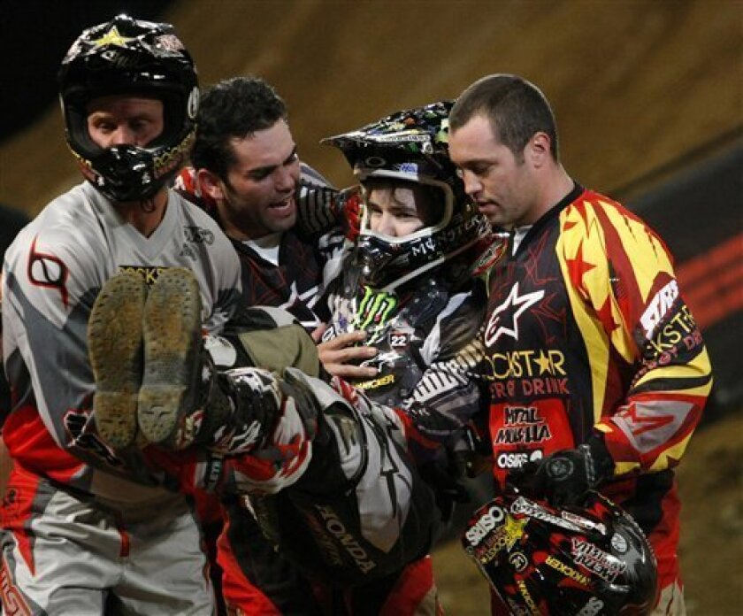 In this Sept. 20, 2008 file photo, Todd Potter, of Temecula, Calif., second from left, talks to Blake Williams, of Australia, as he is carried away by Ronnie Faisst, left, of Murrieta, Calif., and Jeremy Lusk, right, of San Diego, after Williams fell while competing in the Moto X Best Trick competition at the X Games Mexico in Mexico City. Jeremy Lusk, an American freestyle motocross racer, died Monday Feb. 9, 2009, of head injuries two days after crashing while trying to land a backflip in competition in San Jose, Costa Rica. He was 24. (AP Photo/Gregory Bull, File)