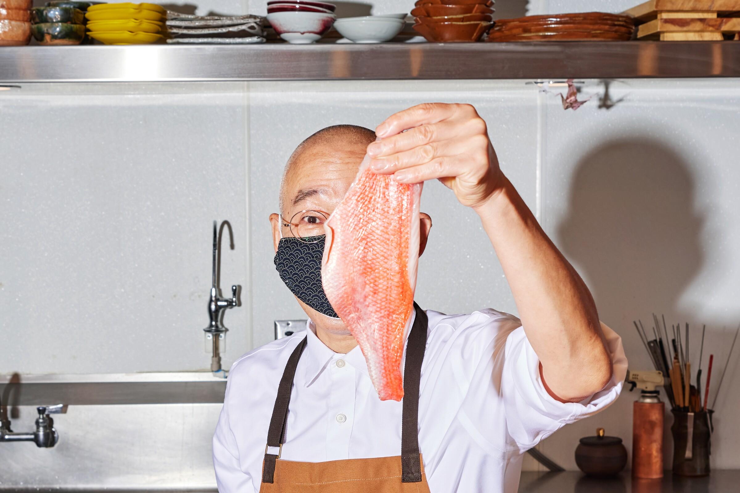 Sushi chef Morihiro Onadera holds up a filleted fish.