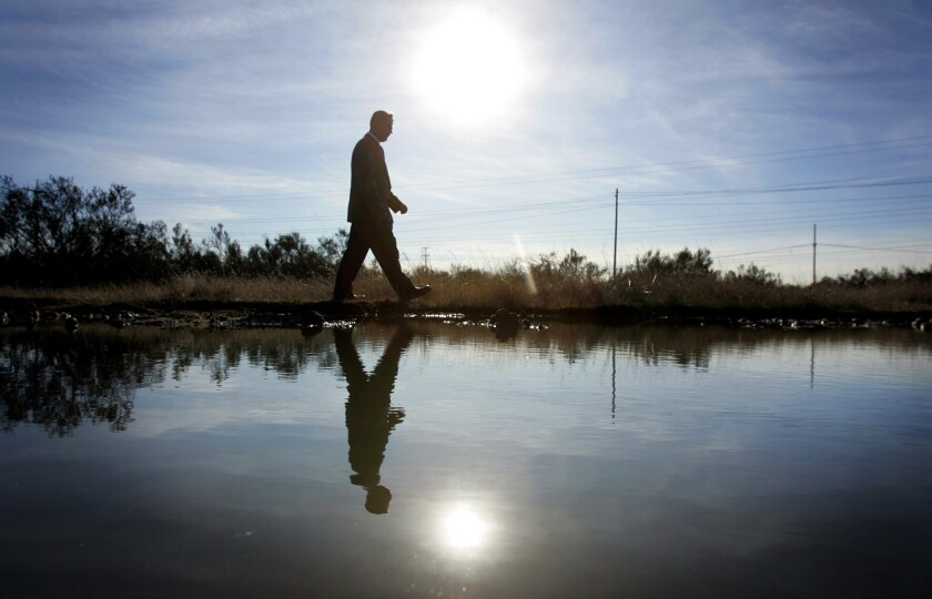 Fort Rosecrans Cemetery director KIRK LEOPARD walks by one the vernal pools on the site. The city of San Diego received a $1 grant to help conserve the seasonal pools.
