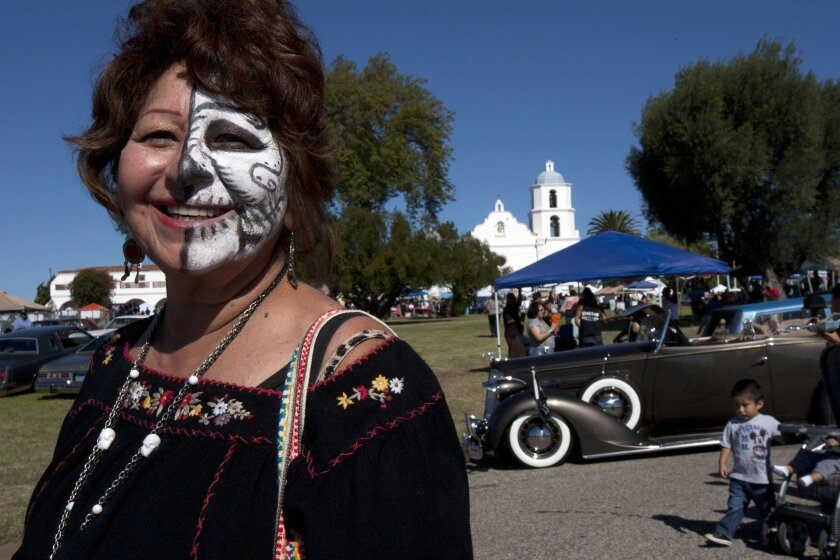 "Maria Elena Gomez of Fallbrook has her face decorated for the occasion during the Dia de los Muertos Festival at Mission San Luis Rey on Oct. 28, 2012. She said she has only half her face painted to represent the duality of the festival, honoring of both the living and the deceased. ""It's almost li"
