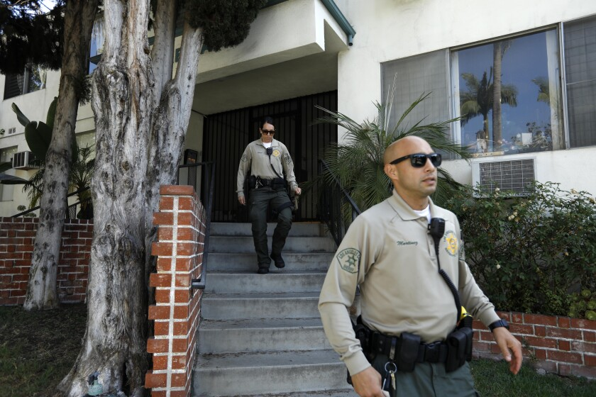 Sheriff's deputies leave the apartment building of Democratic donor Ed Buck