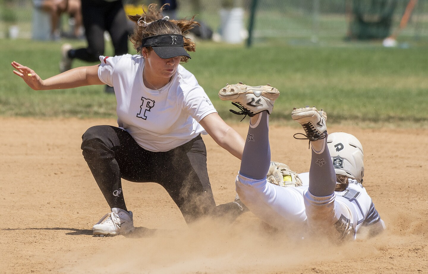 Lakewood Firecrackers's Izzy Pena tags out Texas Bombers's Lourdes Bacon in a 16U Premier softball game in the PGF Nationals in Fountain Valley on Wednesday, August 1.