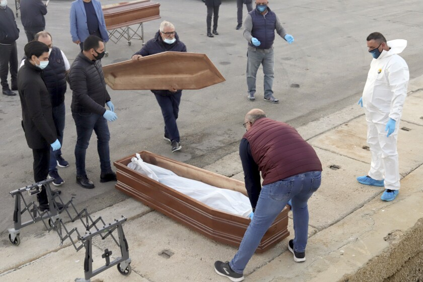 FILE - In this Saturday, Nov. 14, 2020 file photo, a bag containing the body of a migrant who died at sea is placed in a coffin after being disembarked from the Spanish humanitarian rescue ship Open Arms, which was carrying over 200 migrants rescued in the Mediterranean Sea, at the Sicilian port of Trapani, southern Italy. Though the number of migrants and asylum seekers reaching Europe in 2020 is the lowest it has been in the past decade, deaths and disappearances on sea routes to the continent remained alarmingly high with only a small percentage of bodies being recovered according to a report released Friday, March 25, 2021 by UN's migration agency. (AP Photo/Sergi Camara, File)