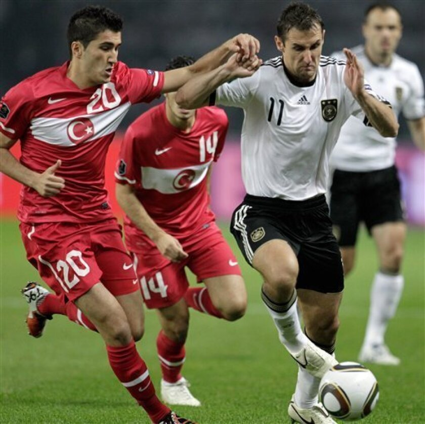 Turkey's Nuri Sahin, left, and Germany's Miroslav Klose, right, challenge for the ball during the Euro 2012 Group A qualifying soccer match between Germany and Turkey in Berlin, Germany, Friday, Oct 8, 2010. (AP Photo/Gero Breloer)