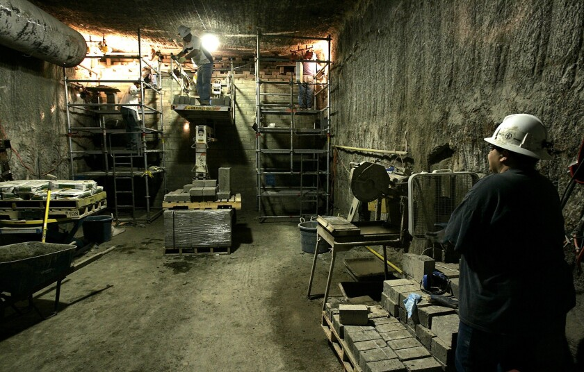 Men seen in 2006 working on setting concrete bricks at the end of one of the Carlsbad Waste Isolation Pilot Plant's salt tunnels. A radiation leak has halted operations at the site.