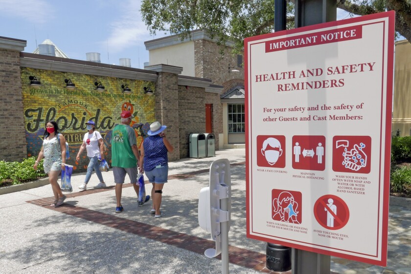FILE - In this June 16, 2020, file photo, signs remind patrons to wear masks and other protocols because of the coronavirus pandemic as they stroll through the Disney Springs shopping, dining and entertainment complex in Lake Buena Vista, Fla. The number of deaths per day from the coronavirus in the U.S. has fallen in recent weeks to the lowest level since late March, even as states increasingly reopen for business. But scientists are deeply afraid the trend may be about to reverse itself. (AP Photo/John Raoux, File)