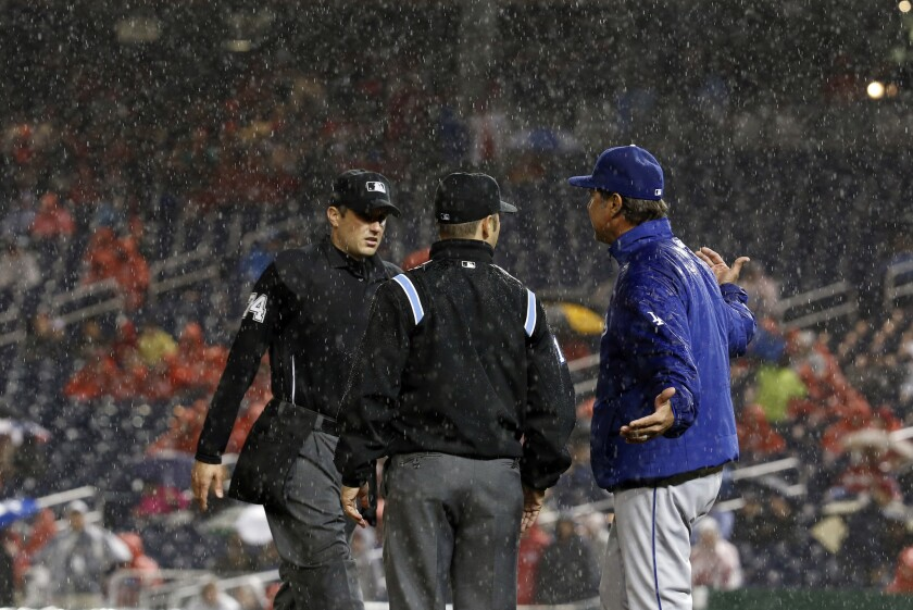 Umpires John Tumpane, left, and Mark Wegner listen to Dodgers Manager Don Mattingly as they discuss a rain delay in the fourth inning in Washington.
