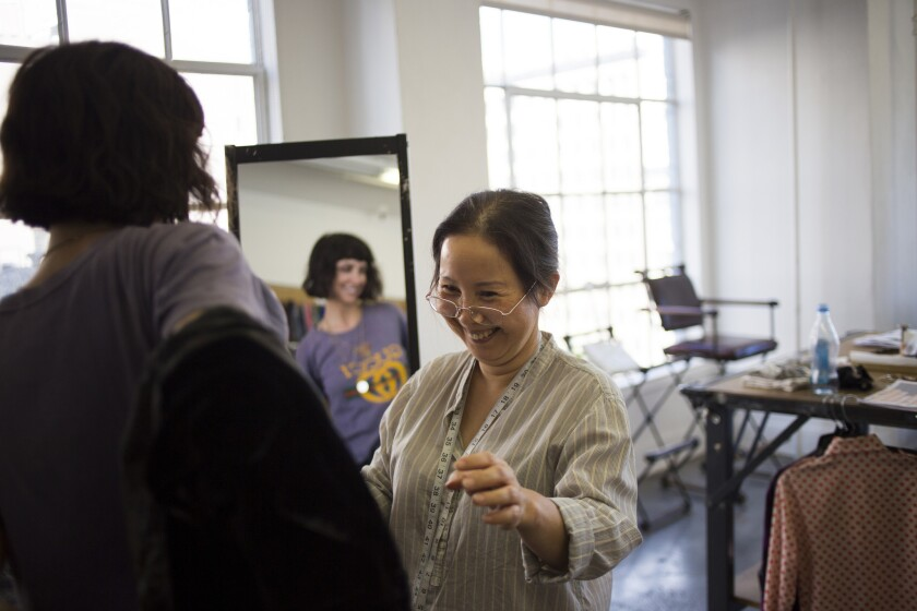 Development pattern maker Helen Do, right, laughs with fashion designer Raquel Allegra as they reconstruct a duster worn by Allegra at her studio in Los Angeles.