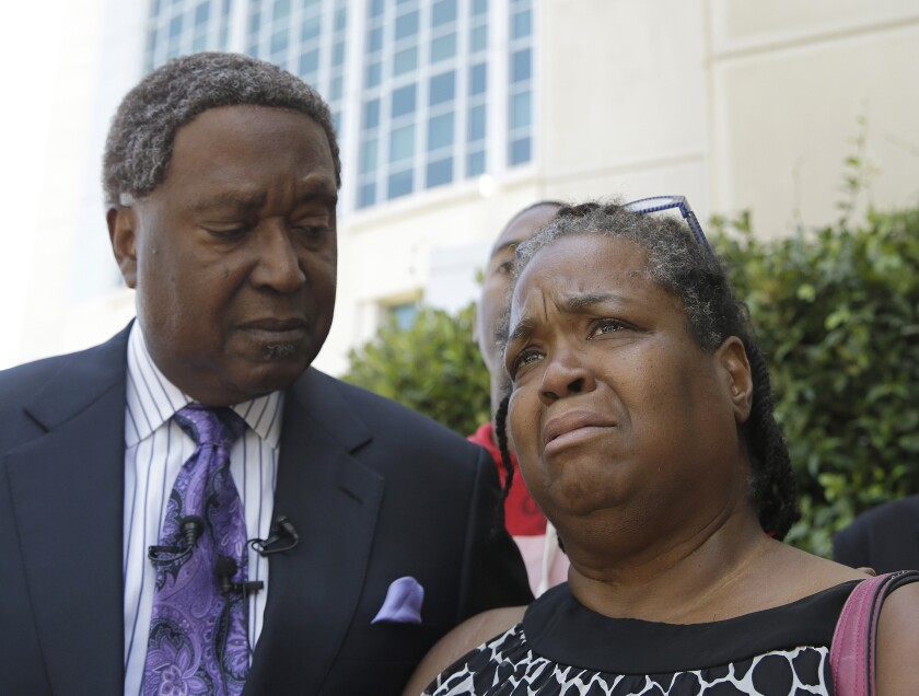 Brigett McIntyre, with attorney John Burris, tears up at a news conference on the police killing of her son in Sacramento