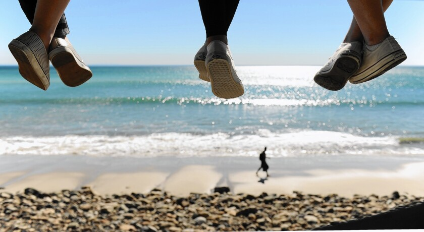On a hot winter day in Malibu, three young girls dangle their feet from a lifeguard tower on Pacific Coast Highway.