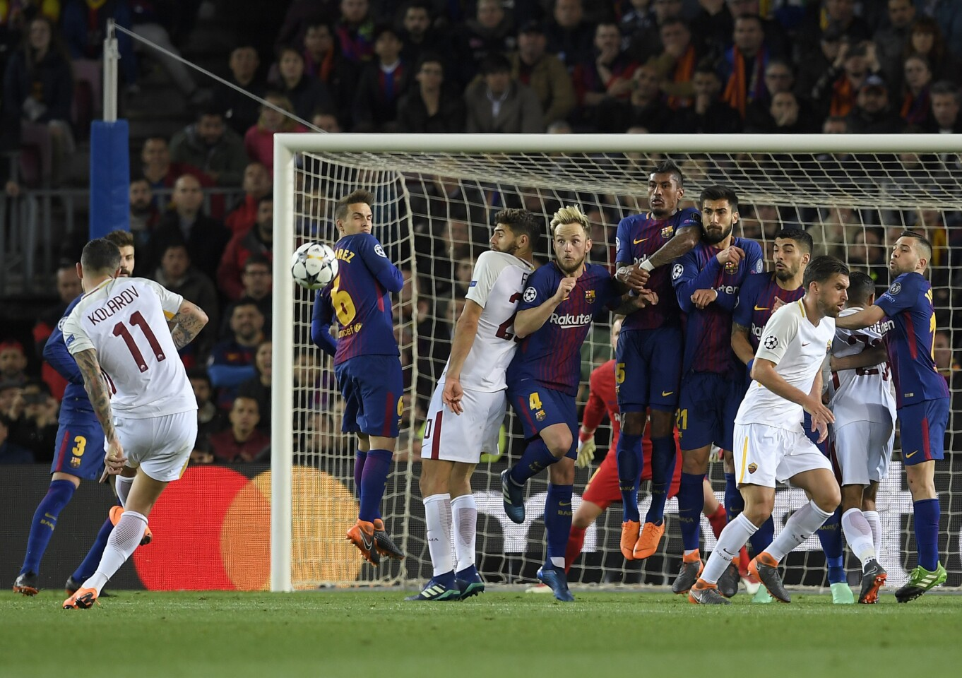 Roma's Serbian defender Aleksandar Kolarov (L) shoots against Barcelona's wall during the UEFA Champions League quarter-final first leg football match between FC Barcelona and AS Roma at the Camp Nou Stadium in Barcelona on April 4, 2018. / AFP PHOTO / LLUIS GENELLUIS GENE/AFP/Getty Images ** OUTS - ELSENT, FPG, CM - OUTS * NM, PH, VA if sourced by CT, LA or MoD **