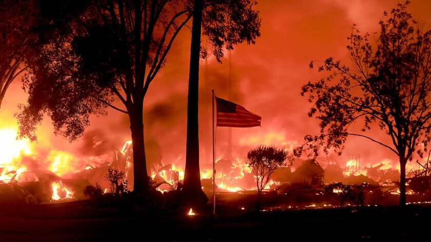 An American flag still fly's as as structures burn in Coffey Park, Monday Oct. 9, 2017. More than a