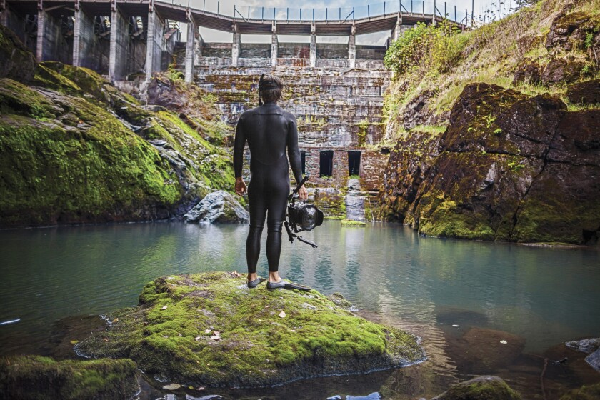 """""""DamNation"""" producer and underwater photographer Matt Stoecker emerges from the icy tail waters below the former Elwha Dam in a scene from the movie """"DamNation."""""""