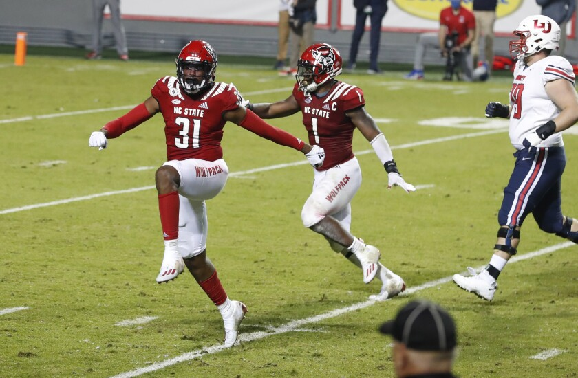 North Carolina State's Vi Jones (31) and Isaiah Moore (1) celebrate after Jones blocked a field goal-attempt by Liberty's Alex Barbir during the second half of an NCAA college football game Saturday, Nov. 21, 2020, in Raleigh, N.C. (Ethan Hyman/The News & Observer via AP, Pool)