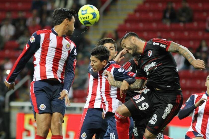 Ángel Zaldívar (c) de Chivas del Guadalajara disputa el balón con Víctor Aguilera (d) de Xolos de Tijuana, durante un partido. EFE/Archivo