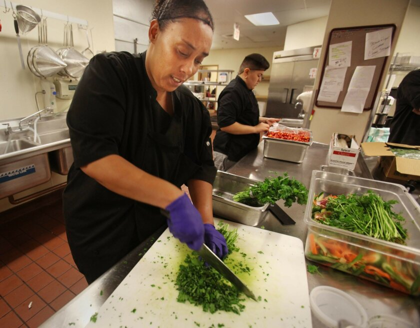 Lekisha Thompson chops parsley for a lunch that will be delivered to the Encinitas Senior Center, the nonprofit's first client. Kitchen partner Nicole Mendoza squeezes lemons for a sauce in the background.