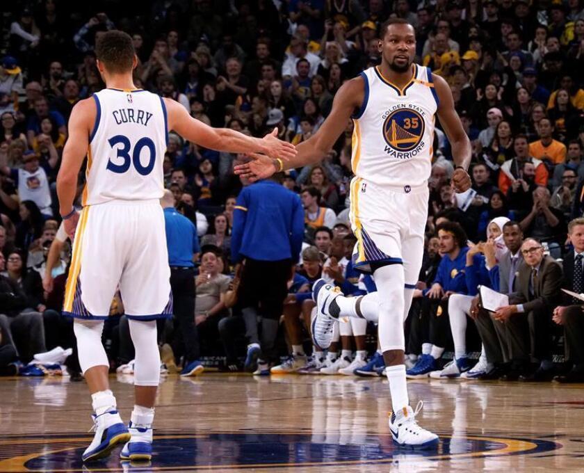 El jugador Stephen Curry (izq) choca los cinco con su compañero Kevin Durant, de los Warriors de Golden State. EFE/Archivo