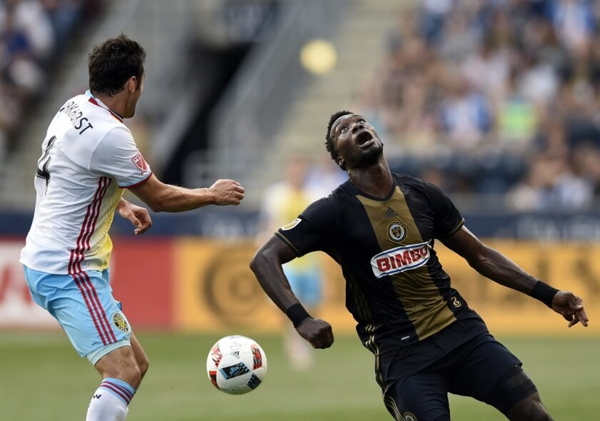 Columbus Crew's Michael Parkhurst (4) kicks the ball away from Philadelphia Union's C.J. Sapong during the first half of an MLS soccer match on Wednesday, June 1, 2016, in Chester, Pa. (AP Photo/Michael Perez)