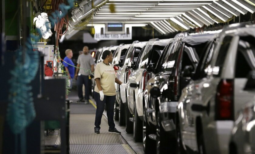 FILE - In this May 13, 2014 file photo, an auto worker inspects finished SUVs coming off the assembly line at the General Motors auto plant in Arlington, Texas. As General Motors tackles a safety crisis, a look at its numbers from June show just how intent the company is on keeping new-car sales on