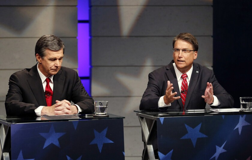 North Carolina Atty. Gen. Roy Cooper, left, a Democrat, was leading Republican Gov. Pat McCrory in a race still too close to call Friday. They are seen here at an Oct. 18 debate.