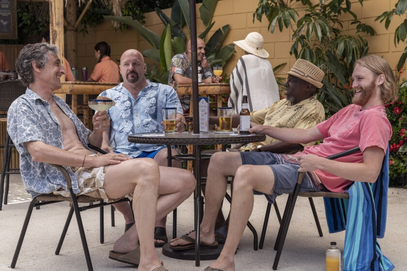 """The cast of """"Lodge 49"""" lounges at a patio table"""